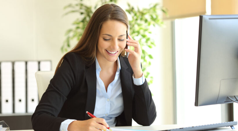 Happy businesswoman calling on mobile phone and taking notes on a desk at office